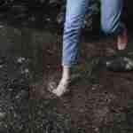 person wearing jeans barefoot in dark soil