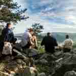 group of young guys sitting on rocky cliff